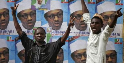 Supporters of presidential candidate Muhammadu Buhari gesture in front of his election posters in Kano March 27, 2015. REUTERS/Goran Tomasevic