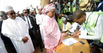 Mohammadu Buhari (left), now Nigeria's president-elect, watches his wife, Aisha, register to vote on March 28, 2015, in Katsina state. PIUS UTOMI EKPEI/AFP/Getty Images